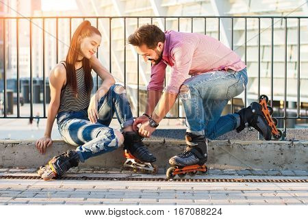 Woman and man wearing rollerblades. Guy is helping a girl. Common hobbies strengthen relationships.