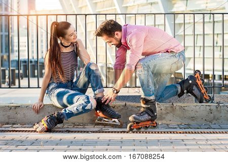 Young couple is wearing rollerblades. Man and woman smiling. In mood for a ride.