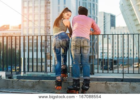 Back view of a couple. People on rollerblades standing. Ready for the ride.