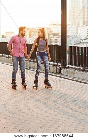 Couple rollerblading and holding hands. People on daytime city background. Let's go for a ride.