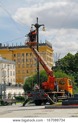 Moscow Russia - June 14 2016: Electricians in bucket at height repair a streetlight in Moscow