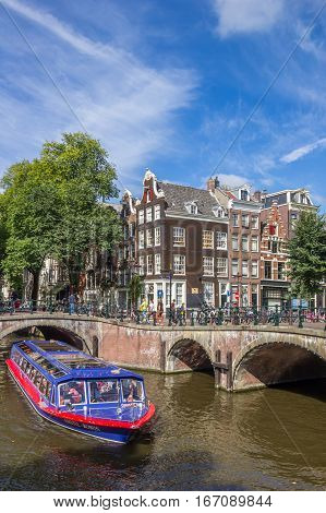 AMSTERDAM, NETHERLANDS - SEPTEMBER 18, 2016: Tourist cruiseboat in the canals of historical Amsterdam, Holland