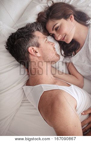 Overhead close up shot of romantic couple lying in bed. Intimate young man and woman looking at each other passionately.