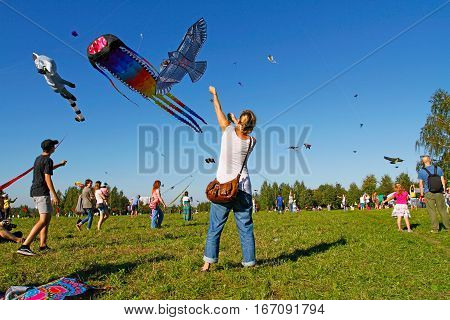 Moscow Russia - August 27 2016: Woman launches a kite into the sky at the kite festival in the Park Tsaritsyno in Moscow