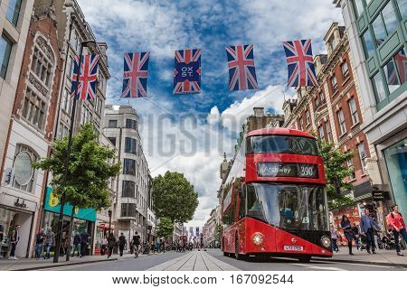 LONDON UK - JUNE 28 2016: A bus passes shoppers and British flags on busy Oxford Street