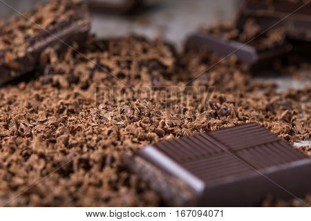 Pile of grated chocolate and broken piece of dark chocolate on wooden rustic background