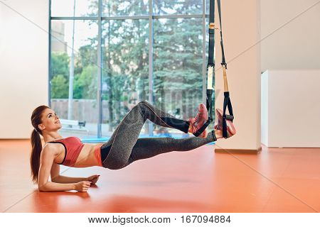 Fit girls in gym doing plank exercise for back spine with trx strap