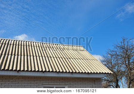 Dangerous asbestos roof tiles on house roof.