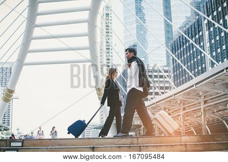 Businessman And Businesswoman Dragging A Suitcase. And Walking Through The Corridor During Rush Hour