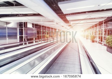 Moving waklway in the airport terminal, travel concept. Backlight