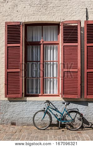 BRUGES BELGIUM - APRIL 24 2010: Bicycle parked by traditional shuttered window on cobbled street