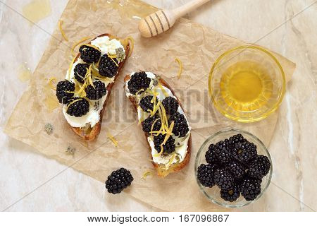 Crostini with goat cheese blackberries lemon zest and honey, top view