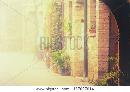 Empty street of small Tuscany town San Quirico d'Orcia in the morning fog, romantic travel vintage hipster european italy background with copy space