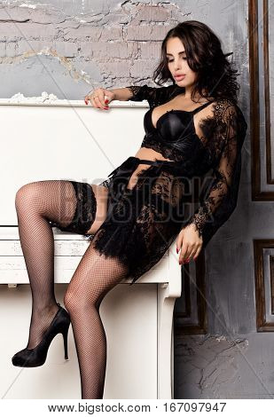 fashion sexy young woman in black lacy lingerie and stockings posing on piano.