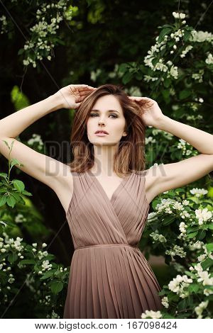 Fashion Spring Model Girl with Brown Hair. Sexy Glamour Beautiful Woman in a Pleated Dress with Flowers Background