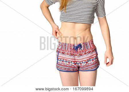 girl pulls the skin on the side. concept of weight loss.