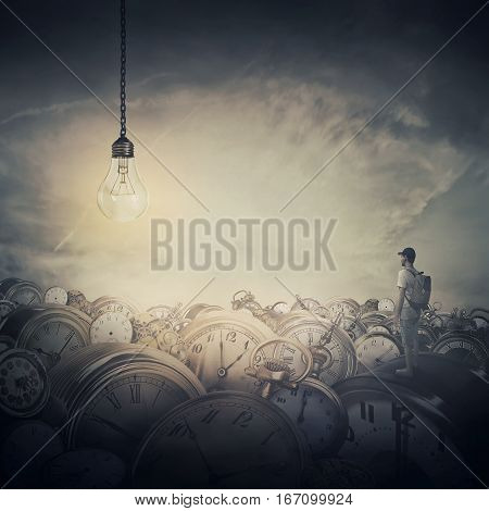 Surreal view as a man with a bag in his back stand in the midle of a clock trash looking at a huge light bulb glowing. Time pressure hour perception and idea concept.