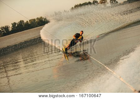Wakeboarder surfing across the lake behind motorboat. Man water skiing on lake with water splashes.