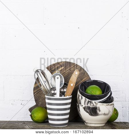 Simple home kitchen still life on a background of bright walls on a wooden shelf with bowls of juicy lime and gray striped ceramic mug with cutlery and kitchen tools.
