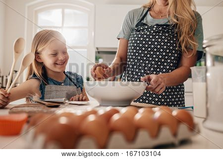 Woman cracking an egg into a bowl with girl standing by in kitchen. Mother and daughter cooking together in kitchen.