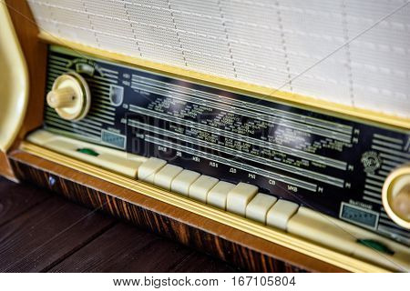Old vintage radio on a wooden background closeup.