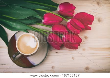 Cup of coffee with spring flowers red tulips on wooden table. Vintage style