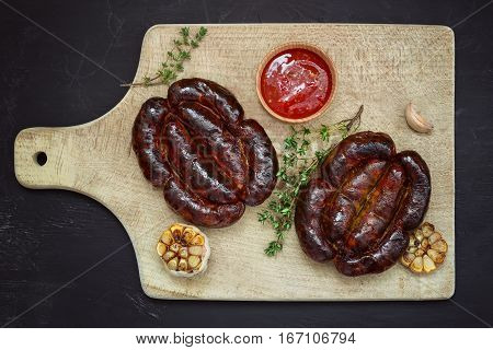 Roasted sausages on wooden board view from above