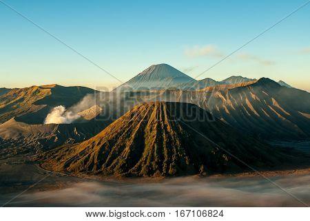 Sunrise at volcano Mount Bromo, clouds swimming around