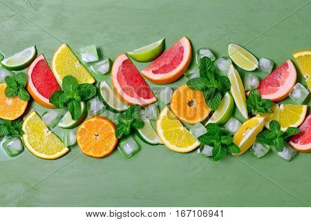 Various citrus fruits mint and ice cubes view from above. Summer cooler concept