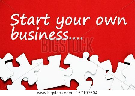 The words start your own business in white text on a red background with white jigsaw puzzle pieces as a metaphor for problem solving
