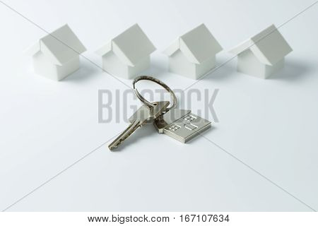 House key in front of a row of miniature white houses
