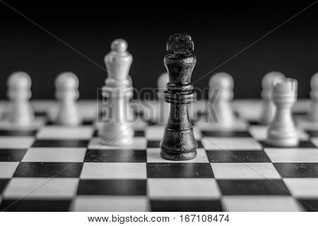 Chess pieces on chessboard and chess king in front, black and white photography.