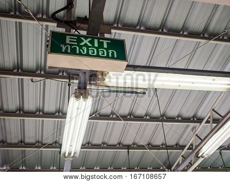 Exit sign with thai word means exit under old factory roof
