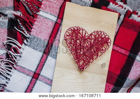Handmade heart shape of the threads on wood desk and cashmere blanket in red, white, black tartan. Flat layout, top view