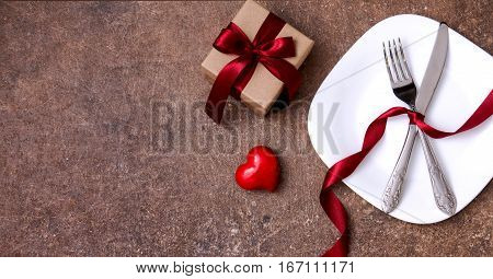 Festive table setting for Valentines Day or Wedding with a fork, knife and hearts on a dark wooden table. The view from the top.
