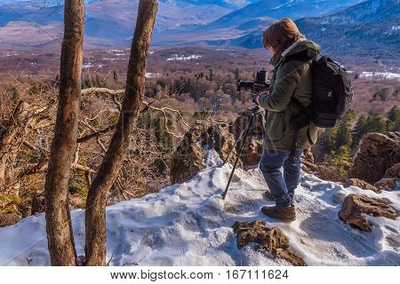 Wildlife and outdoor photographer with camera on the edge of rock observing winter forest