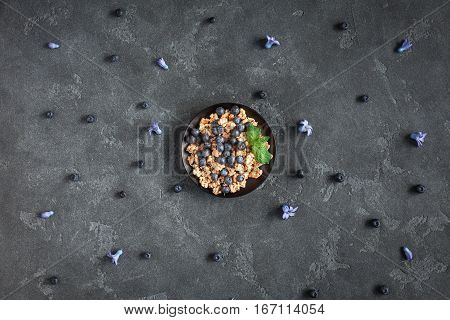 Healthy breakfast with muesli and berries on black background. Flat lay top view