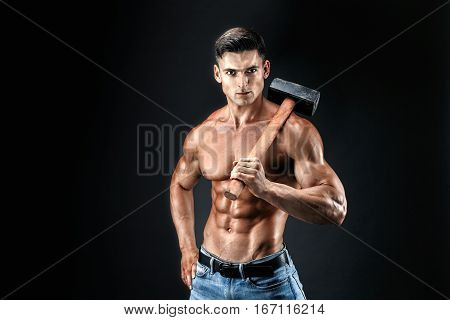 Muscular man with naked torso holding big hummer. Isolated on dark grey background