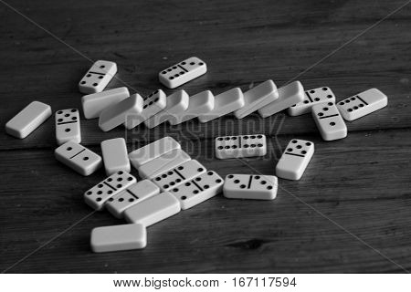 Domino effect - white came piece on wooden table in black and white style