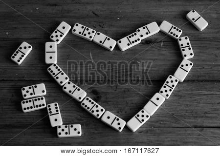 Love heart shape of domino pieces on wooden background on black and white style