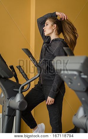 Photo of young pretty woman with long hair training in s crosstrainer in a gym