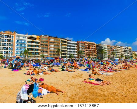 Lloret de mar Spain - September 13 2015: The people resting at the sand on beach at seafront in Lloret de mar Spain on September 13 2015