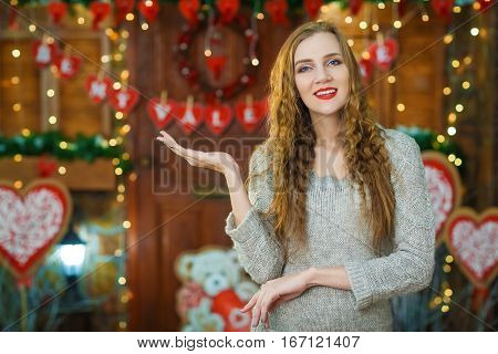 Portrait of young woman showing a product - empty copy space on the open hand palm, over Valentines day background