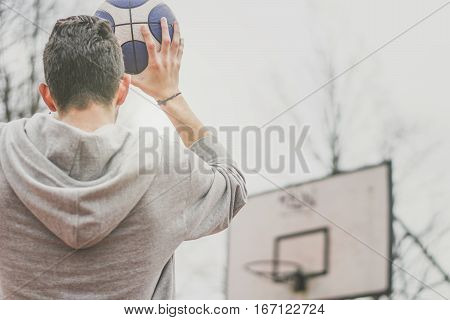 Street basketball player shooting hoops at the basketball court outdoor - Back view of a young man playing basket with a blue and white ball making a score - sport and people concept