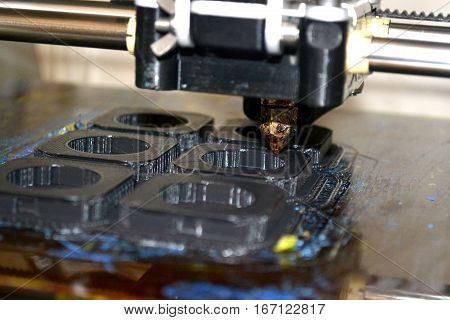 Modern 3D printer printing figure close-up macro. Automatic three dimensional 3d printer performs plastic modeling in laboratory.
