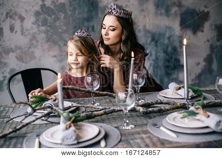 mother and daughter in the image of the queen and princess dresses in the colors of Marsala the Christmas table