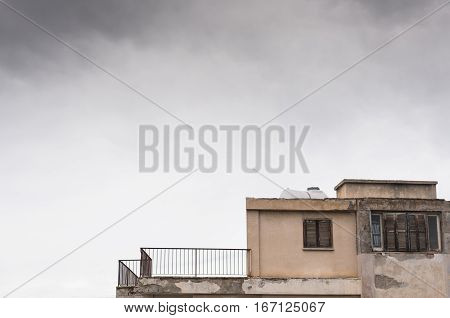 Apartment house in a very bad condition and cloudy overcast sky