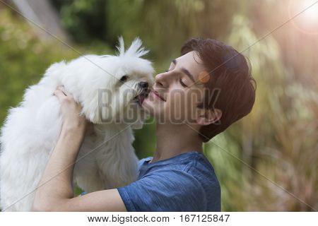 Teenage boy holds white maltese dog on a garden background