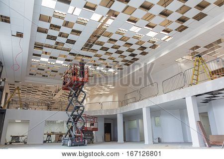ST ALBANS UK - JULY 8 2016: Electricians install ceiling lights using scissor lift in large building