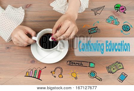 Continuing Education. Coffee cup top view on wooden table background.